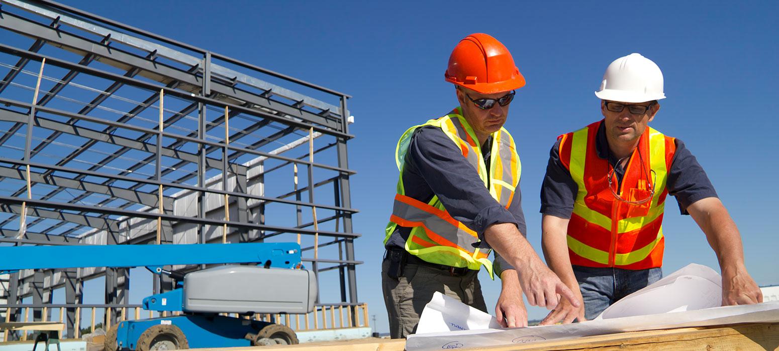 2 workers checking drawings by metal framework